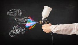 O homem com pintura à pistola do aerógrafo com carro, o barco e a motocicleta tiram Fotos de Stock