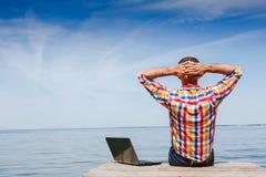 O homem com portátil aprecia o trabalho exterior Fotos de Stock Royalty Free