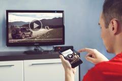 O homem com Smartphone conectou a um vídeo de observação da tevê em casa imagens de stock royalty free