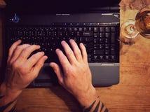 O homem com tatuagens trabalha no portátil Fotos de Stock