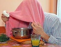 O homem com toalha respira vapores do bálsamo para tratar frios e a gripe Fotos de Stock Royalty Free