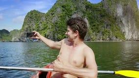 O homem com torso desencapado faz Selfie no caiaque contra Rocky Island video estoque