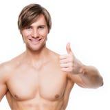O homem com torso muscular mostra os polegares acima do sinal Imagens de Stock