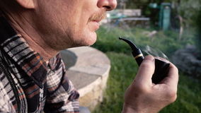 O homem com um bigode fuma uma tubulação no ar livre vídeos de arquivo