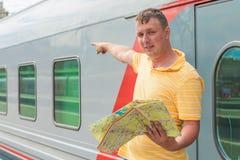 O homem com um mapa mostra o sentido do estação de caminhos-de-ferro Fotografia de Stock Royalty Free