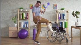 O homem com um pé enfaixado quebrado joga muletas como uma guitarra mo lento video estoque