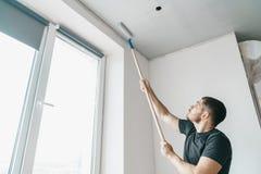 O homem com um rolo em suas mãos pinta o teto na cor cinzenta perto da janela de sua casa foto de stock