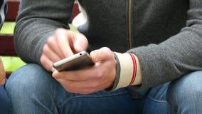 O homem com um smartphone em suas mãos mostra algo a uma a outra pessoa e gesticular vídeos de arquivo