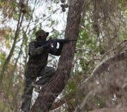 O homem com uma arma em uma árvore encontra o inimigo foto de stock