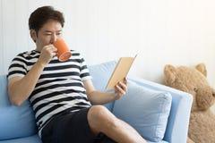 O homem com uma caneca e a leitura de um livro para relaxam na sala de visitas em ho fotos de stock royalty free