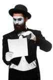 O homem com uma cara mimica a leitura com da ampliação Fotografia de Stock Royalty Free