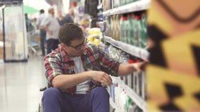 O homem com uma inabilidade em uma auto loja da cadeira de rodas escolhe os bens video estoque