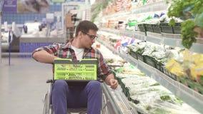 O homem com uma inabilidade em uma cadeira de rodas escolhe os bens na compra no fim do supermercado acima video estoque