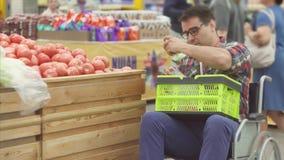 O homem com uma inabilidade em uma compra da cadeira de rodas no supermercado escolhe tomates e põe-nos em um pacote Fim acima filme