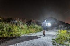 O homem com uma lanterna de incandescência brilhante em sua mão vai na noite fotografia de stock