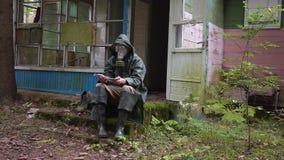 O homem com uma máscara de gás na paisagem apocalíptico conta o dinheiro, e joga-o então afastado video estoque
