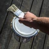 O homem com uma m?o forte leva uma lata da pintura sobre o terra?o e guarda uma escova, reparo em uma casa privada, um pla de tra imagens de stock