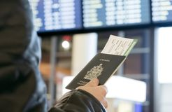O homem com uma passagem canadense do passaporte e de embarque olha a partida imagens de stock
