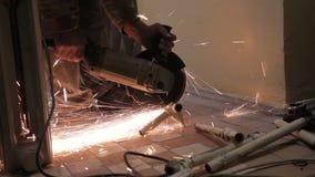 O homem com uma serra circular com faíscas brilhantes corta uma parte de uma tubulação velha vídeos de arquivo