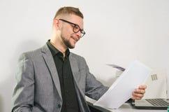 O homem com vidros e revestimento sorri estudando originais Imagens de Stock Royalty Free