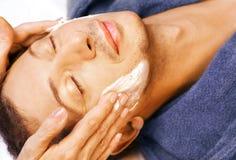 O homem começ a massagem de creme na face Foto de Stock Royalty Free