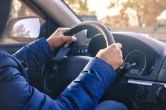 O homem começa conduzir um carro A mão está na roda fotos de stock