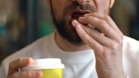 O homem come cookies de uns pedaços de chocolate e o café bebendo em um café filme