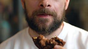 O homem come cookies de uns peda?os de chocolate em um caf? vídeos de arquivo