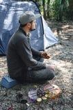 O homem come espetos grelhados deliciosos do vegetariano em carv?es, em vegetais, em abobrinha e em cogumelos ardentes no molho d imagens de stock