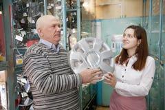 O homem compra as tampas de roda automotrizes Foto de Stock Royalty Free