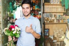 O homem compra flores em um florista mantendo um ramalhete disponivel imagens de stock royalty free