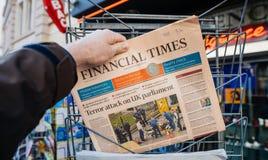 O homem compra o jornal financeiro das épocas do quiosque da imprensa após L imagens de stock royalty free