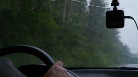 O homem conduz um carro no tempo chuvoso filme