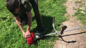 O homem conduz uma trança da gasolina Puxa agudamente o cabo começando video estoque