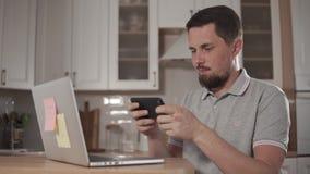 O homem considerável adulto está jogando em um smartphone na casa, vestindo fones de ouvido filme