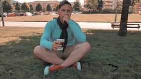 O homem considerável artístico relaxa no parque do distrito da cidade vídeos de arquivo
