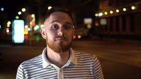 O homem considerável com barba olha acima e então in camera Vestido em camisa listrada e em suporte na rua na noite filme