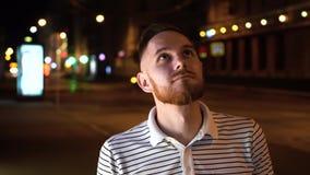 O homem considerável com barba olha acima e então in camera Vestido em polo e em suporte listrados na rua na noite vídeos de arquivo
