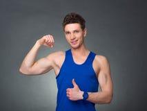 O homem considerável com braços cruzou a vista de sua esquerda no fundo preto Foto de Stock