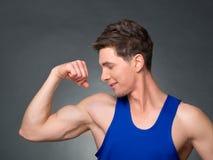 O homem considerável com braços cruzou a vista de sua esquerda no fundo preto Imagem de Stock Royalty Free