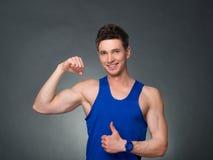 O homem considerável com braços cruzou a vista de sua esquerda no fundo preto Fotografia de Stock Royalty Free