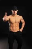 O homem considerável do halterofilista que mostra os polegares levanta o sinal com um torso despido Fotos de Stock