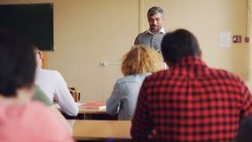 O homem considerável do professor alto está falando aos estudantes que se estão sentando em tabelas na sala de aula e no sorriso  filme