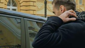 O homem considerável endireita seus revestimento e lenço que olham na janela de seu carro filme