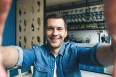 O homem considerável está fazendo fotos no café imagens de stock royalty free