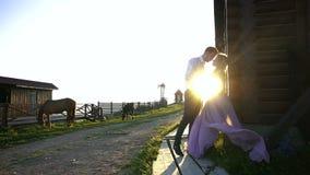 O homem considerável está guardando as mãos, narizes tocantes e está beijando-as com sua amiga loura encantador no vestido roxo l vídeos de arquivo