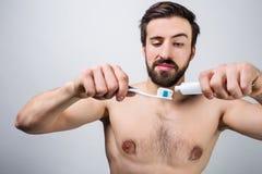 O homem considerável está preparando-se para escovar seus dentes Outting alguma pasta de dente na escova de dentes Fim acima Cort Foto de Stock