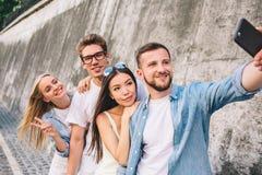 O homem considerável farpado está estando na frente de seus amigos e está tomando o selfie com eles Estão estando um em seguida imagem de stock
