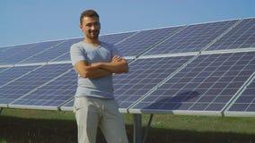 O homem considerável mostra o polegar acima no fundo dos painéis solares filme