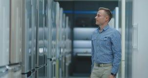 O homem considerável na camisa azul abre a porta do refrigerador na loja de dispositivos e compara-a com outros modelos para comp video estoque